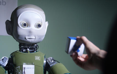 Humanoid robot staring at a colored cube held by a human