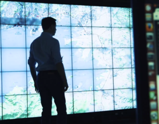 Man standing in front of wall of screens.