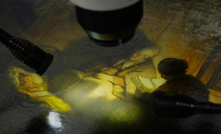 close-up shot of a painting being examined by a microscope