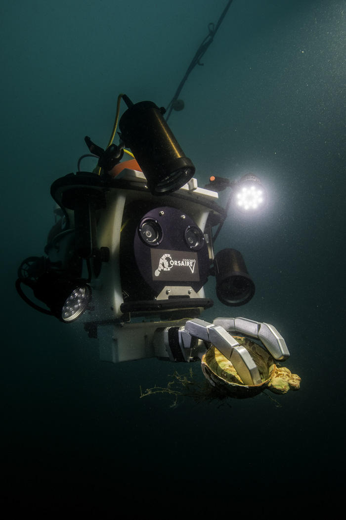 Robot in a dark water. it is grasping an archaeological object in its claw which is illuminated by a headlamp