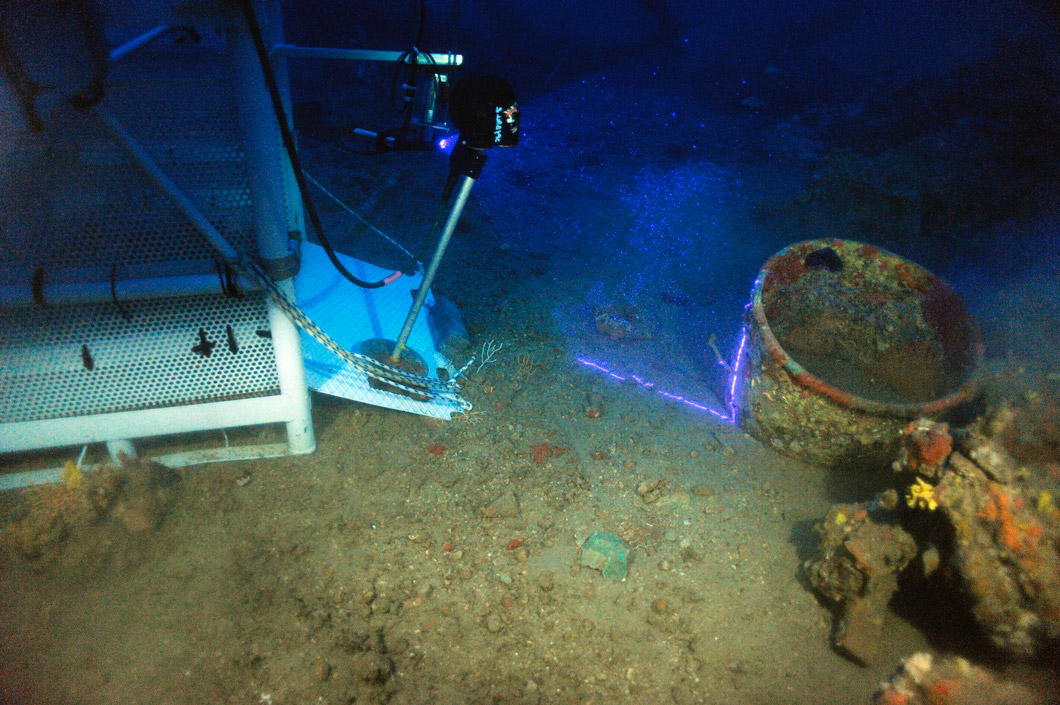 On the site of a shipwreck, a machine scans ancient pottery with a violet beam.