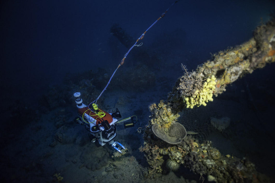 The robot is on the sea floor. In the foreground: a boat anchor. A cable is visible attached to the robot.