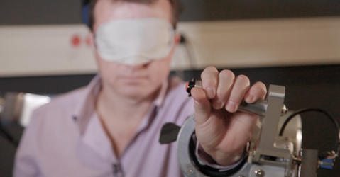 Blindfolded man holding a device that measures wrist positions