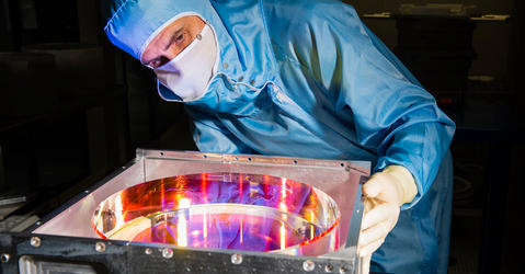 Engineer observing the reflective surface of a high precision mirror