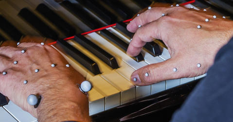 Hands of a piano player with motion capture markers.