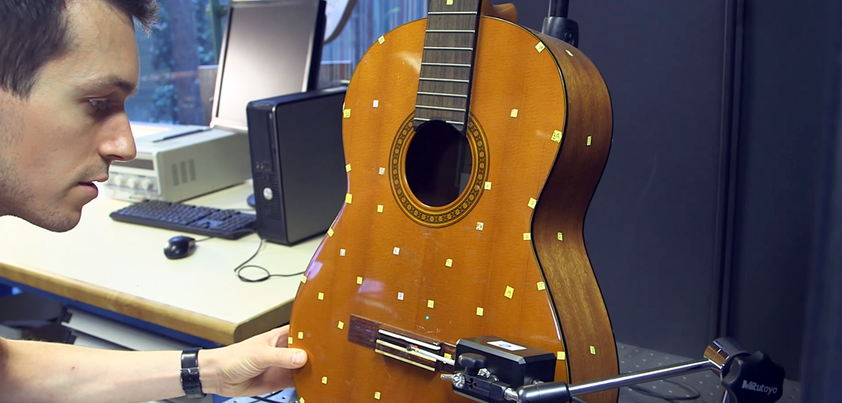 Physicist studying the acoustics of a guitar